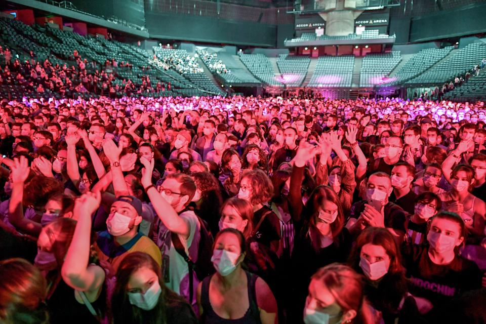 People cheer during a concert of French DJ Etienne de Crecy and pop band Indochine, aimed at scientifically testing the safety level toward the Covid-19 infection and the possibilities of reopening live events amidst the pandemic, at the AccorHotels Arena in Paris on May 29, 2021. (Photo by STEPHANE DE SAKUTIN / AFP) (Photo by STEPHANE DE SAKUTIN/AFP via Getty Images)
