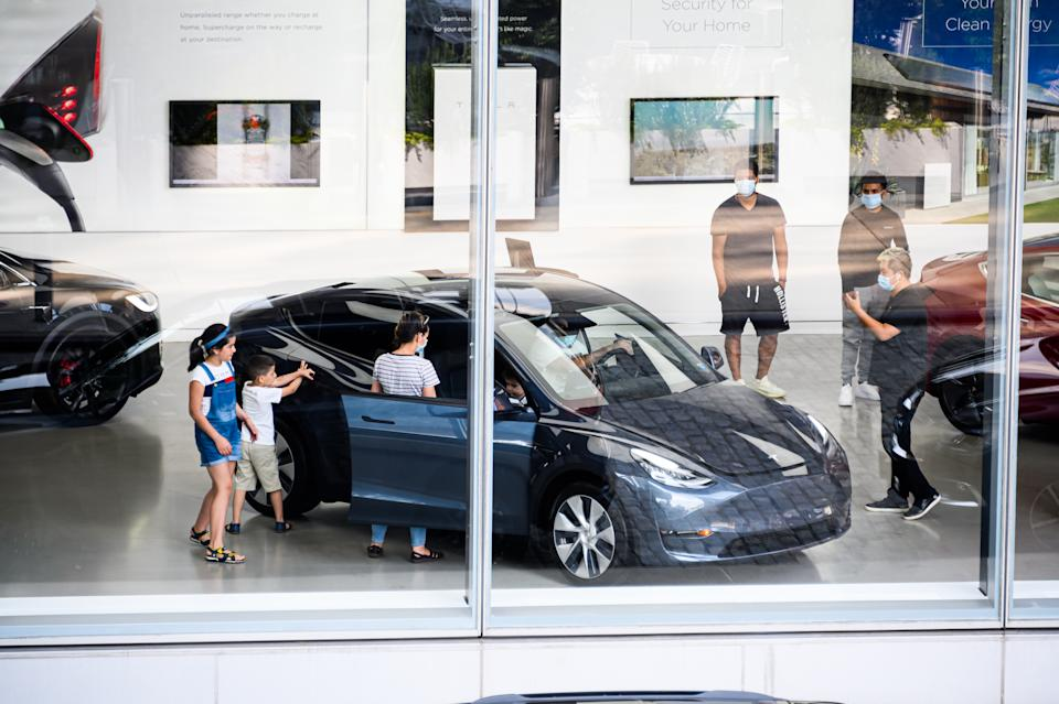 NEW YORK, NEW YORK - JULY 16: People wear face masks inside the Tesla dealership in Chelsea as New York City moves into Phase 3 of re-opening following restrictions imposed to curb the coronavirus pandemic on July 16, 2020. One of New York City's most popular attractions, the High Line re-opened with social distancing policies as part of the Phase 3 coronavirus plan. (Photo by Noam Galai/Getty Images)