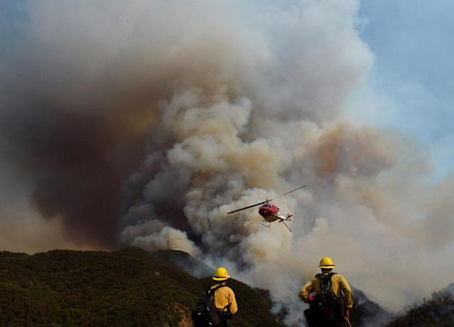 <p>Los Padres National Forest firefighters watch as helicopters work on the northeast flank of the Whittier fire near Hot Spring Canyon outside Cachuma Lake, California, U.S. July 11, 2017. (Mike Eliason/Santa Barbara County Fire/Handout via Reuters) </p>