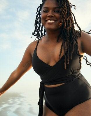 """<h2>Aerie Wrap One-Piece Swimsuit</h2><br>Now, if you're wondering what the <a href=""""https://refinery29.com/en-us/best-black-one-piece-swimsuit"""" rel=""""nofollow noopener"""" target=""""_blank"""" data-ylk=""""slk:best black one-piece swimsuit"""" class=""""link rapid-noclick-resp"""">best black one-piece swimsuit</a> looks like, take a gander: this classic-DVF-reminiscent wrap suit from Aerie was a by-far-and-away reader favorite. Reviewers love it for its versatility as a full-coverage suit with the look of a two-piece style and customizable support with removable padding and adjustable straps.<br><br><em>Shop <strong><a href=""""https://www.ae.com/us/en/p/aerie/one-piece-swimsuits/scoop-one-piece-swimsuits/aerie-wrap-one-piece-swimsuit/0751_1200_073"""" rel=""""nofollow noopener"""" target=""""_blank"""" data-ylk=""""slk:Aerie"""" class=""""link rapid-noclick-resp"""">Aerie</a></strong></em><br><br><strong>Aerie</strong> Wrap One Piece Swimsuit, $, available at <a href=""""https://go.skimresources.com/?id=30283X879131&url=https%3A%2F%2Fwww.ae.com%2Fus%2Fen%2Fp%2Faerie%2Fone-piece-swimsuits%2Fscoop-one-piece-swimsuits%2Faerie-wrap-one-piece-swimsuit%2F0751_1200_073"""" rel=""""nofollow noopener"""" target=""""_blank"""" data-ylk=""""slk:AE"""" class=""""link rapid-noclick-resp"""">AE</a>"""
