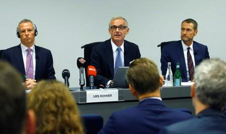 Chairman Rohner of Swiss bank Credit Suisse sits between Tiner, Chairman of the Audit Committee and Romerio, Managing Partner of Homburger during a news conference in Zurich