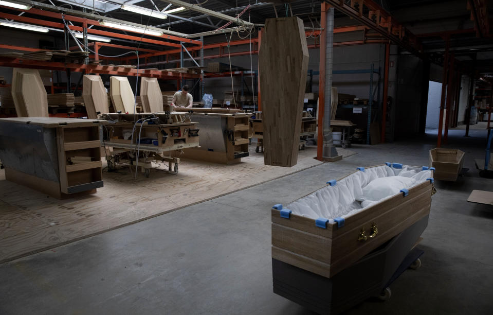 """FILE - In this Thursday, April 9, 2020 file photo, an employee at a woodworking station works on a section of a casket at the production warehouse of Aninco in Peer, Belgium. After the European Union passed the death toll of half a million citizens lost to the coronavirus on Wednesday, Feb. 10, 2021, the EU Commission chief said that stalling rollout of the vaccines could be partly blamed on the bloc being over-optimistic, over-confident and plainly """"too late."""" (AP Photo/Virginia Mayo, File)"""