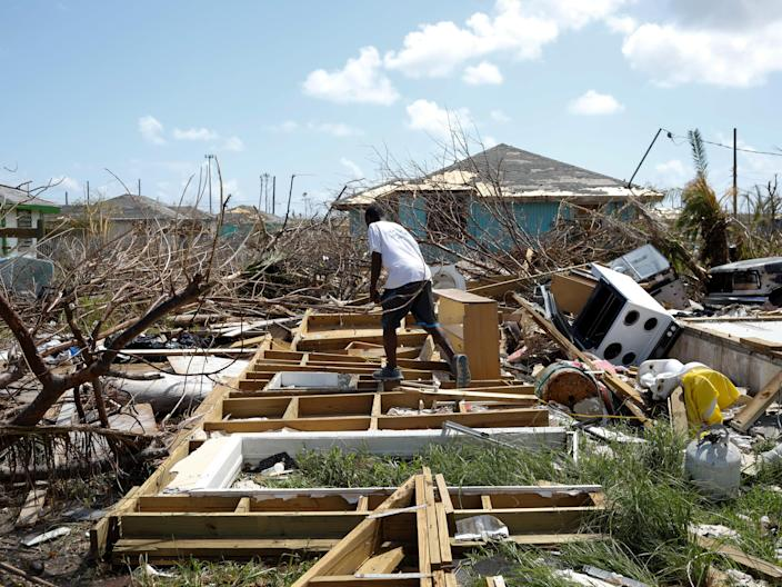 FILE PHOTO: A man walks among the debris of his house after Hurricane Dorian hit the Abaco Islands in Spring City, Bahamas, September 11, 2019. REUTERS/Marco Bello - RC1D219815D0/File Photo
