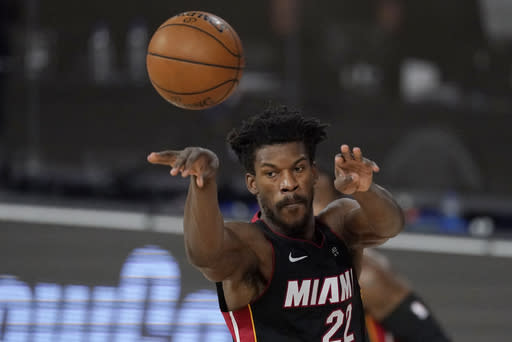 Miami Heat's Jimmy Butler (22) passes in the first half of an NBA conference semifinal playoff basketball game against the Milwaukee Bucks Tuesday, Sept. 8, 2020 in Lake Buena Vista, Fla. (AP Photo/Mark J. Terrill)