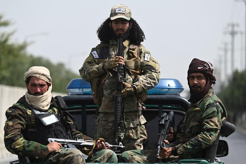 Armed Taliban fighters pictured while veiled women march at a pro-Taliban rally in Kabul on 11 September (AFP via Getty Images)