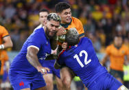 Australia's Noah Lolesio, centre, is tackled by France's Arthur Vincent, right, and Romain Taofifenua during the third rugby international between France and Australia at Suncorp Stadium in Brisbane, Australia, Saturday, July 17, 2021. (AP Photo/Tertius Pickard)