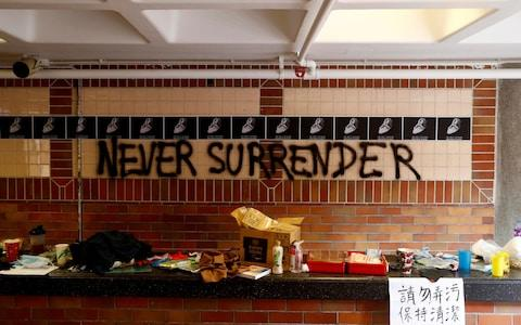 """The slogan """"Never Surrender"""" is spray painted on a wall in the besieged Hong Kong Polytechnic University (PolyU) in Hong Kong, China - Credit: REUTERS"""