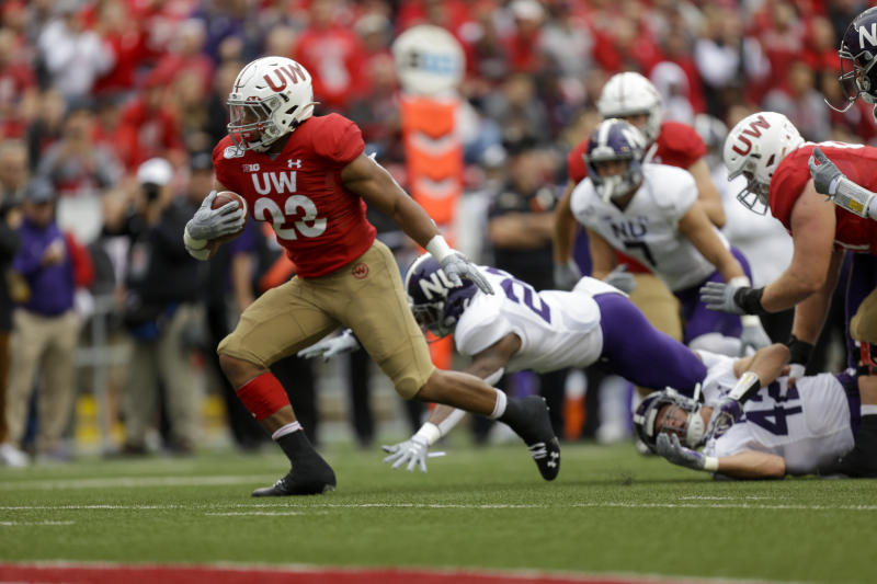 Wisconsin running back Jonathan Taylor (23) run for a touchdown against Northwestern defensive back Brian Bullock (26) and Northwestern linebacker Paddy Fisher (42) during the first half of an NCAA college football game Saturday, Sept. 28, 2019, in Madison, Wis. (AP Photo/Andy Manis)