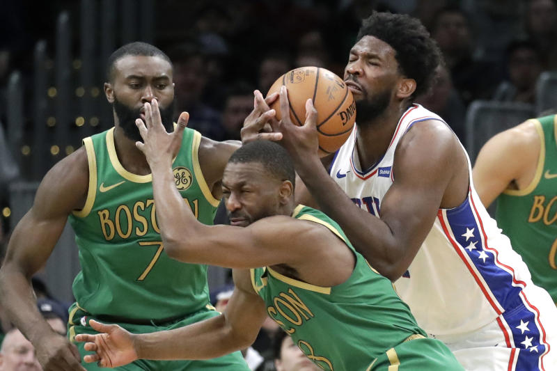 Philadelphia 76ers center Joel Embiid controls the ball against Boston Celtics guards Kemba Walker (8) and Jaylen Brown (7) in the second half of an NBA basketball game, Thursday, Dec. 12, 2019, in Boston. The 76ers won 115-109. (AP Photo/Elise Amendola)