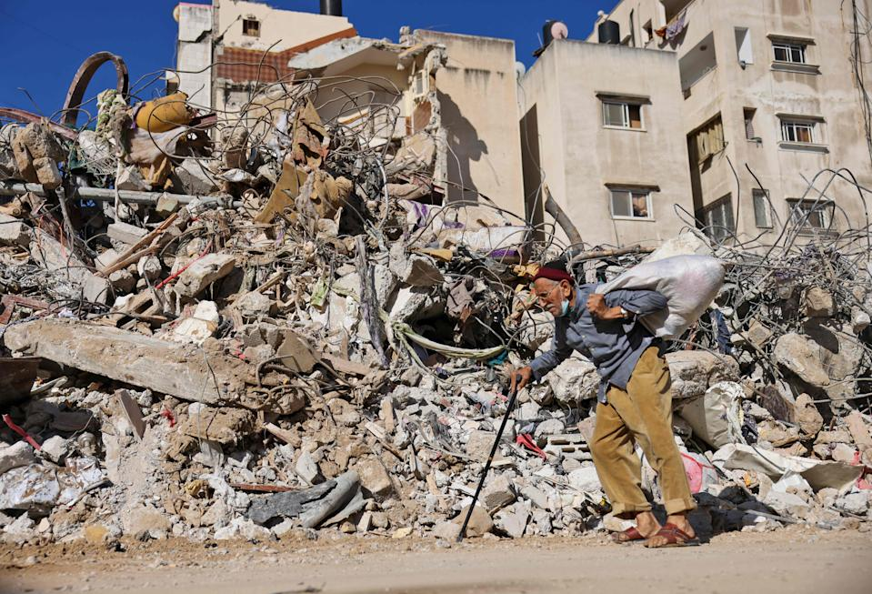 <p>A Palestinian man walks past a building destroyed by Isreali shelling in Gaza City</p> (AFP via Getty Images)