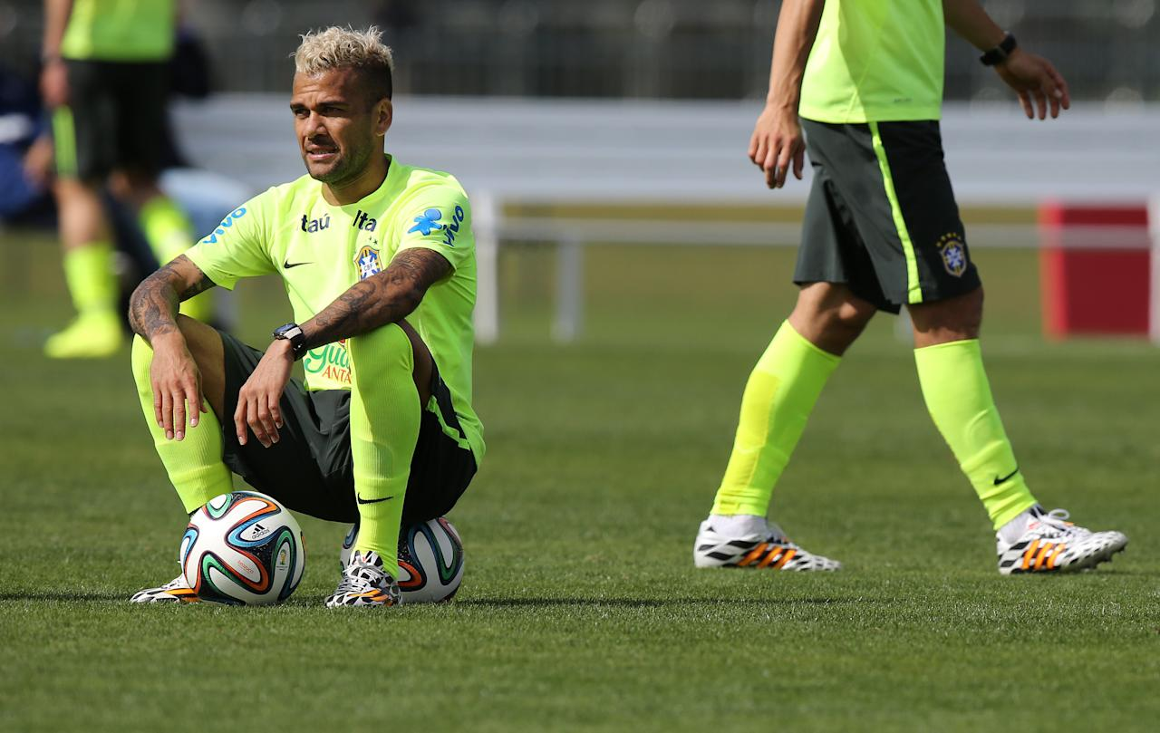 Brazil's Daniel Alves sits on a ball during a practice session at the Granja Comary training center, in Teresopolis, Brazil, Monday, July 7, 2014. Brazil will face Germany on Tuesday in a World Cup semifinal match without Neymar. (AP Photo/Leo Correa)