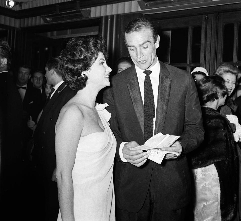 <p>At the 1962 premiere of <em>Dr. No, </em>James Bond actor Sean Connery reviews his tickets while co-star Zena Marshal looks on. The film served as the first big-screen outing for Agent 007 and has since spawned 25 James Bond sequels. </p>