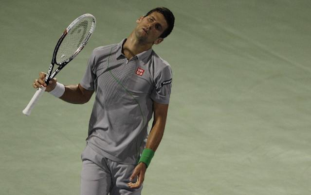 Novak Djokovic of Serbia reacts after he missed a ball against Roger Federer of Switzerland during a semi final match of the Dubai Tennis Championships in Dubai, United Arab Emirates, Friday, Feb. 28, 2014. (AP Photo/Kamran Jebreili)