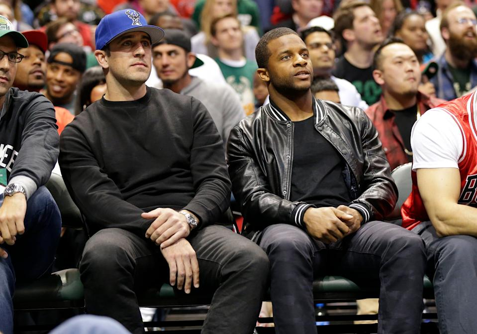 Green Bay Packers quarterback Aaron Rodgers (left) and Packers wide receiver, Randall Cobb watch the action during Game 3 of the Bucks-Bulls series in the NBA Playoffs.