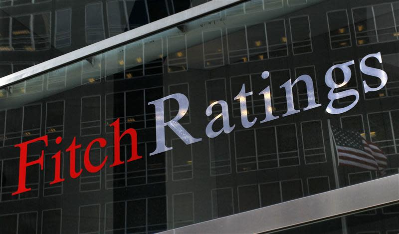 A flag is reflected on the window of the Fitch Ratings headquarters in New York in this February 6, 2013, file photo. REUTERS/Brendan McDermid/Files