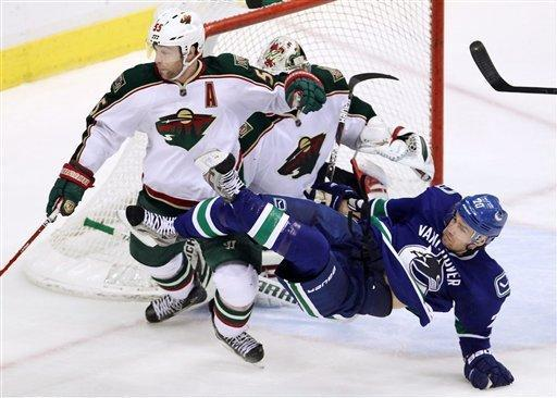 Minnesota Wild defenseman Nick Schultz (55) tries to clear Vancouver Canucks left wing Christopher Higgins (20) from in front of Minnesota Wild goalie Niklas Backstrom (32) during third period NHL hockey action at Rogers Arena in Vancouver, British Columbia, Monday, Dec, 19, 2011. (AP Photo/The Canadian Press, Jonathan Hayward)