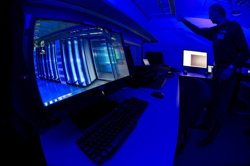 FILE - This Friday Jan. 11, 2013 file photo of a member of the Cybercrime Center as he turns on the light in a lab during a media tour at the occasion of the official opening of the Cybercrime Center at Europol headquarters in The Hague, Netherlands. The European Union police agency says that cybercriminals are using new technology and exploiting existing online vulnerabilities as they shift their focus to larger and more profitable targets. (AP Photo/Peter Dejong, File)