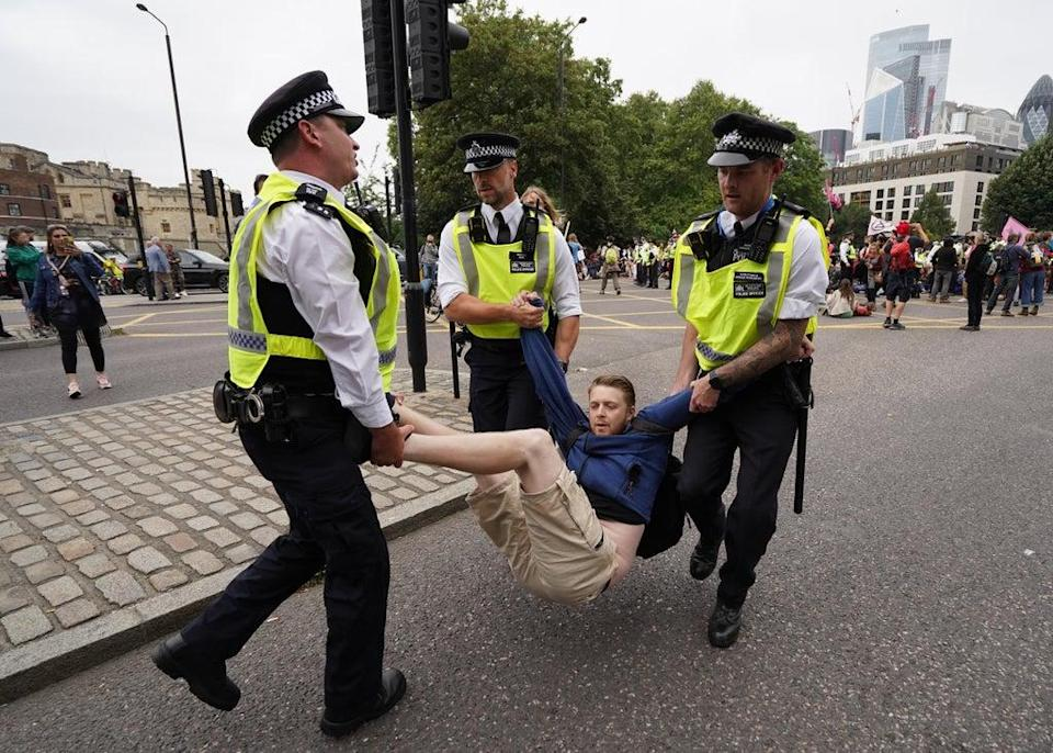 Police remove a man as members of Extinction Rebellion reach Tower Hill during their march in central London. (PA/Stefan Rousseau) (PA Wire)