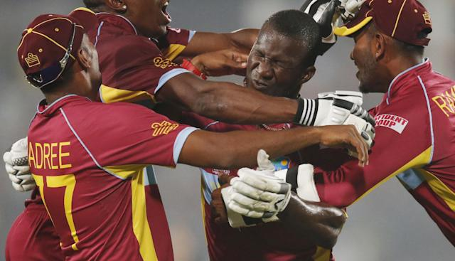 10ThingstoSeeSports - West Indies' players pounce on captain Darren Sammy, second right, to celebrate their win over Australia in the ICC Twenty20 Cricket World Cup match in Dhaka, Bangladesh, Friday, March 28, 2014. West Indies won the match by six wickets. (AP Photo/Aijaz Rahi, File)