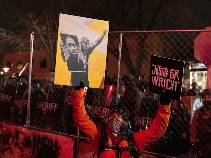 """<p>A demonstrator holding a poster of George Floyd and sign reading """"Justice for Wright"""" in front of a line of police officers outside the Brooklyn Center police station while protesting the death of Daunte Wright who was shot and killed by a police officer in Brooklyn Center, Minnesota on 14 April 2021</p> ((AFP via Getty Images))"""