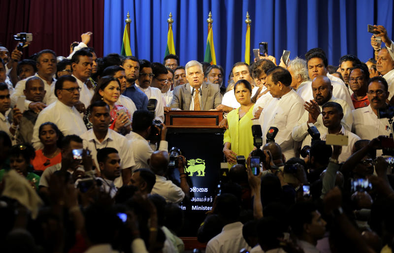 In this Sunday, Dec. 16, 2018, file photo, Sri Lanka's reinstated Prime Minister Ranil Wickremesinghe, center, surrounded by his loyal lawmakers and supporters speaks after assuming duties in Colombo, Sri Lanka. Government dysfunction and an intelligence failure that preceded the Easter Sunday bombings that killed 253 people in Sri Lanka are traced to simmering divisions between the president and prime minister after a weekslong political crisis that crippled the country last year. (AP Photo/Eranga Jayawardena, File)