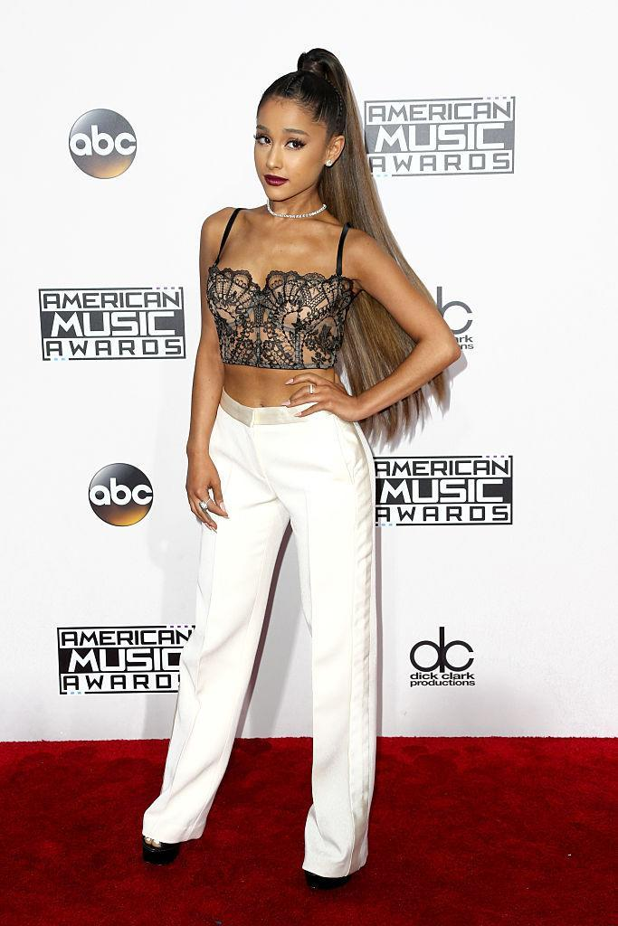 <p>Ariana Grande paired conservative white trousers with a lace bustier top. The tiny pop star's signature ponytail was longer than usual with some extra extensions. <em>(Photo: Getty Images)</em> </p>