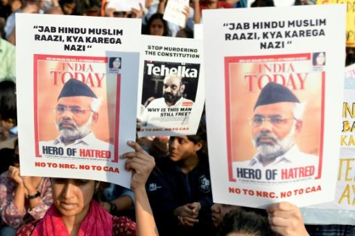 Protesters in Bangalore, opposed to a new citizenship law promoted by Indian Prime Minister Narendra Modi's government, hold placards featuring a years-old magazine cover with his picture