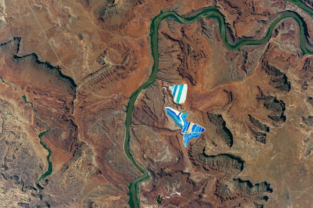 "<p>A photo taken on Aug. 9, 2017 by an astronaut aboard the International Space Station of solar evaporation ponds outside the city of Moab, Utah, part of a operation to mine potassium chloride — €"" more commonly referred to as muriate of potash (MOP) —€"" from ore buried underground. Each pond color indicates a different state of evaporation. The deep blue color is from a dye added to ponds of potash brine and water in order to speed up the rate of heat absorption. The seafoam green indicates shallower waters that are well into the evaporation process. The tan colored ponds are nearly dry; salt crystals (the final product) are left over in the pond and ready for collection. (Photo: NASA/Handout via Reuters) </p>"