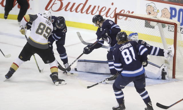 Winnipeg Jets' Josh Morrissey (44) and Jacob Trouba (8) defend Vegas Golden Knights' Alex Tuch (89) as goaltender Laurent Brossoit (30) gets his pad out to stop the puck during the third period of an NHL hockey game Tuesday, Jan. 15, 2019, in Winnipeg, Manitoba. (Trevor Hagan/The Canadian Press via AP)