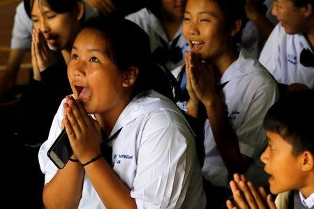 FILE PHOTO: Classmates pray after their teacher announced some of the 12 schoolboys trapped inside a flooded cave have been rescued, at Mae Sai Prasitsart school, in the northern province of Chiang Rai, Thailand July 9, 2018. REUTERS/Tyrone Siu/File Photo