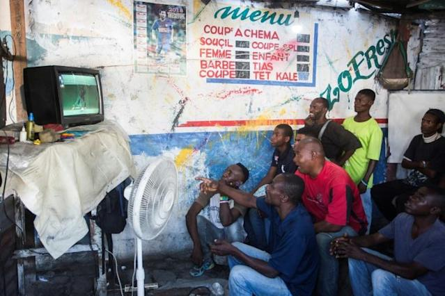 Haitians watch the World Cup Group Stage match between Argentina and Iceland in a small hairdresser on the troittoir in downtown Port-au-Prince, Haiti (AFP Photo/Pierre Michel Jean)
