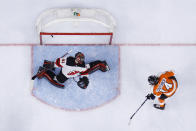 Philadelphia Flyers' Sean Couturier (14) gets a shot past New Jersey Devils' Scott Wedgewood (41) during the second period of an NHL hockey game, Monday, May 10, 2021, in Philadelphia. (AP Photo/Matt Slocum)