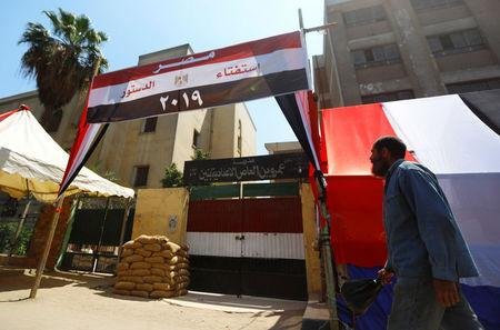 An Egyptian man walks in front of a school used as a polling station covered from outside by Egyptian flags, during the preparations for the upcoming referendum on constitutional amendments in Cairo