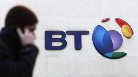A man talks on his mobile telephone as he walks past a BT logo in London