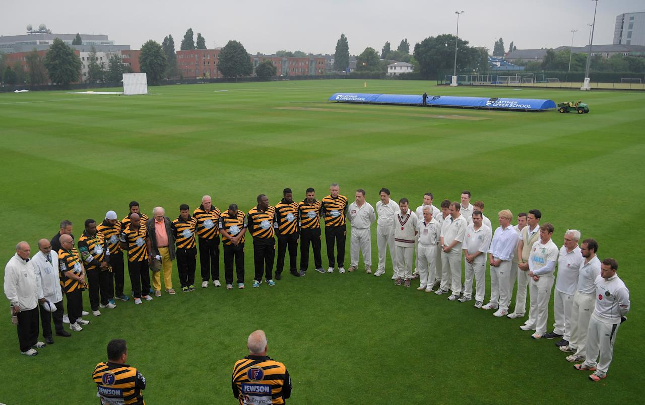 British lawmakers (R) and former international cricketers (L) stand for a minute of silence ahead of a charity cricket match to remember and support the victims of the Grenfell Tower fire in London, Britain June 27, 2017. REUTERS/Toby Melville