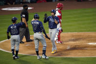 Tampa Bay Rays' Willy Adames, center right, is high-fived by Austin Meadows (17) after Adames scored on a single by Mike Brosseau during the third inning of a baseball game against the Los Angeles Angels Monday, May 3, 2021, in Anaheim, Calif. (AP Photo/Marcio Jose Sanchez)