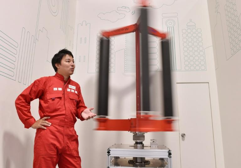 Engineer Atsushi Shimizu, founder and CEO of the Japanese venture company Challenergy, stands next to his bladeless wind turbine in Tokyo