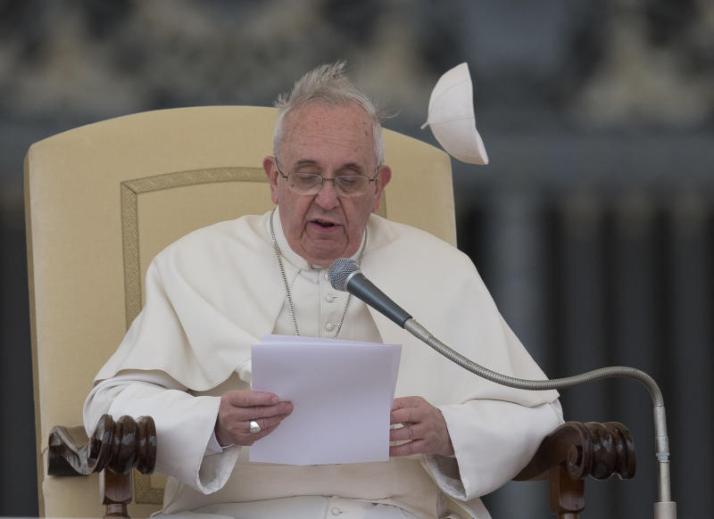 A gust of wind blows away Pope Francis' cap as he delivers his message during his weekly general audience in St. Peter's Square at the Vatican, Wednesday, Feb. 19, 2014. (AP Photo/Alessandra Tarantino)