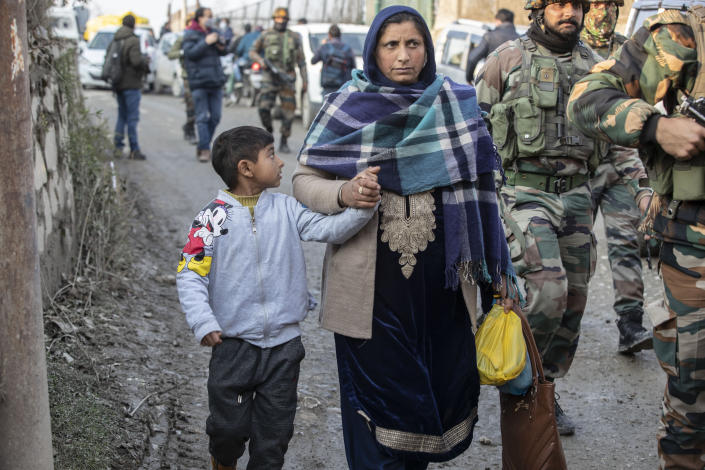 Kashmiris walk past security officers patrolling near the site of an attack on the outskirts of Srinagar, Indian controlled Kashmir, Thursday, Nov. 26, 2020. Anti-India rebels in Indian-controlled Kashmir Thursday killed two soldiers in an attack in the disputed region's main city, the Indian army said.(AP Photo/Mukhtar Khan)