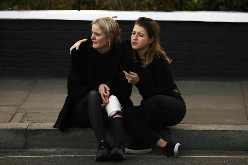 An injured woman reacts outside Parsons Green tube station. (Reuters)