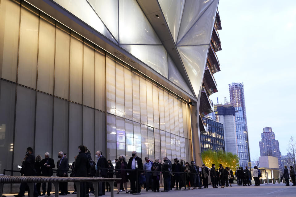 People line up outside The Shed before a live performance by the New York Philharmonic, whose members performed together for the first time since March 2020, on Wednesday, April 14, 2021, at Hudson Yards in New York. Normal subscription performances are to resume in September. (AP Photo/Kathy Willens)