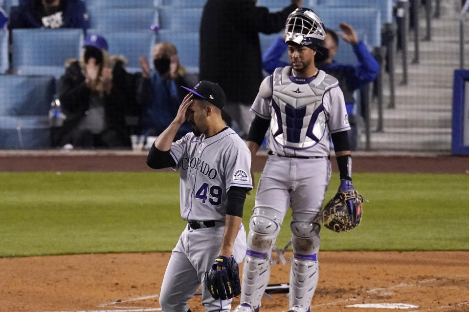Colorado Rockies starting pitcher Antonio Senzatela, left, wipes his face as catcher Elias Diaz watches after Los Angeles Dodgers' Corey Seager scored on a single by Gavin Lux during the third inning of a baseball game Tuesday, April 13, 2021, in Los Angeles. (AP Photo/Mark J. Terrill)