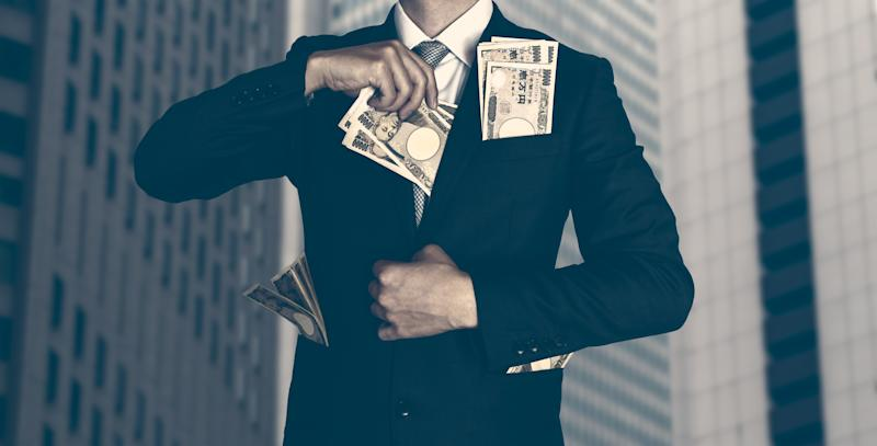 Pictured: Billionaire in business suit stuffs banknotes into pockets. Image: Getty