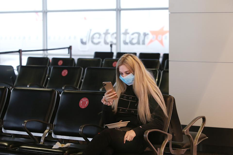 A woman wearing a face mask sits in an airport boarding area as a Jetstar plane is seen through the window.