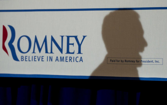 A shadow is cast on a placard by Republican presidential candidate, former Massachusetts Gov. Mitt Romney, as he campaigns in Metairie, La., Friday, March 23, 2012. (AP Photo/Steven Senne)