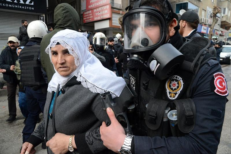 A member of the Turkish riot police detains a woman on January 17, 2016, after having disperse demonstrators protesting curfew in Sur district in the centre of Diyarbakir (AFP Photo/Ilyas Akengin)
