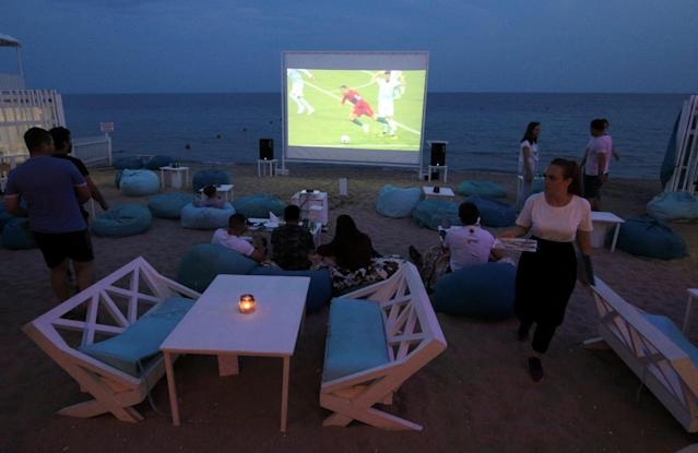 FILE PHOTO: Soccer Football - World Cup - Group B - Portugal vs Spain - Yevpatoria, Crimea - June 15, 2018. People watch the match at a cafe. REUTERS/Pavel Rebrov/File Photo