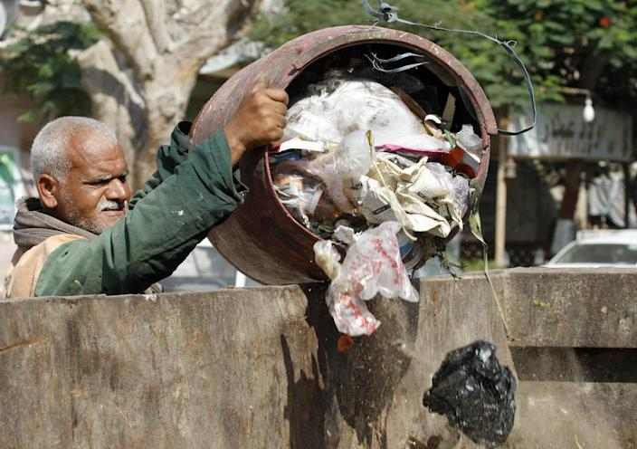 In this Thursday, Aug. 16, 2012 photo, a waste collector unloads garbage at a container in Cairo. A government modernization effort flopped. A swine flu panic prompted the mass slaughter of the pigs that recycled Cairo's organic garbage; the city's metal trash bins were easy prey for thieves, especially during the global scrap metal boom. Now the garbage crisis in the Arab world's biggest city is posing a significant test for the newly elected government that replaced longtime autocratic leaders. (AP Photo)