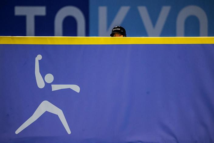The hat and eyes of a person are visible over a barrier that has the logo of a softball pitcher.