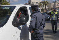 A Palestinian police officer issues a ticket to a motorists who is not wearing a face mask, part of the recent preventative health measures due to the surge of COVID-19 cases, in the West Bank city of Ramallah, Thursday, Feb. 25, 2021. (AP Photo/Nasser Nasser)